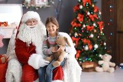 La petite fille s'asseyant sur le ` authentique de Santa Claus enroulent à l'intérieur images libres de droits