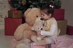 La petite fille s'asseyant sur le plancher avec deux tailles différentes jouent des ours attendant Santa le réveillon de Noël Photo libre de droits
