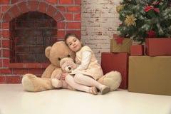 La petite fille s'asseyant sur le plancher avec deux tailles différentes jouent des ours attendant Santa le réveillon de Noël Photographie stock