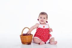 La petite fille s'assied avec des cerises de panier images stock