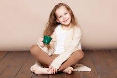 La petite fille s'assied avec une tasse sur le plancher photos stock