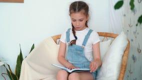 La petite fille s'assied dans le fauteuil, tient le livre et lit dedans la chambre à coucher, mouvement lent banque de vidéos