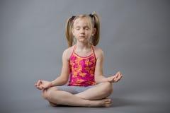 La petite fille s'assied dans une méditation de pose Photographie stock