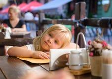La petite fille s'assied en café de rue Images stock