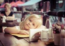 La petite fille s'assied en café de rue Image libre de droits