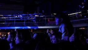 La petite fille s'assied sur l'épaule de l'homme dans le hall serré, observe la représentation sur l'étape clips vidéos