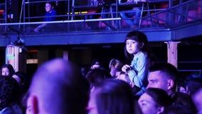 La petite fille s'assied sur l'épaule de l'homme dans le hall serré, observe la représentation sur l'étape banque de vidéos