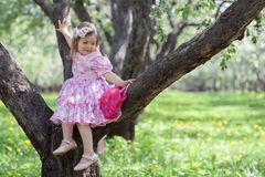 La petite fille s'assied sur l'arbre Photo stock