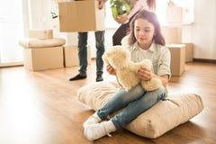 La petite fille s'assied sur l'oreiller sur le plancher et regarde à son jouet d'ours de nounours Elle a un certain repos tandis  Photographie stock