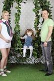 La petite fille s'assied sur l'oscillation et le père et la mère Image stock
