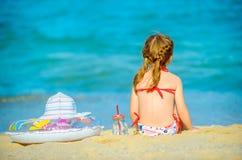 la petite fille s'assied sur le bord de la mer et examine la distance photographie stock libre de droits