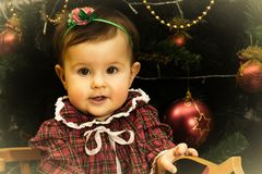 La petite fille s'assied sur le cheval en bois devant Christmass TR photographie stock