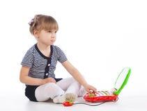 La petite fille s'assied sur le plancher avec l'ordinateur portable et le regard de jouet Photo stock