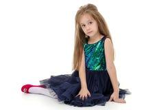 La petite fille s'assied sur le plancher photo libre de droits