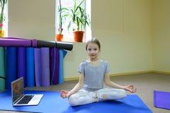 La petite fille s'assied sur le plancher en position de lotus images stock