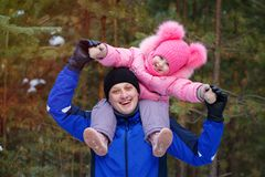 La petite fille s'assied sur ses épaules du ` s de père dans la forêt d'hiver photo stock