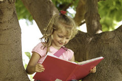 La petite fille s'assied sur un grand arbre au parc et lit un livre photos libres de droits