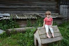 la petite fille s'assied sur un petit dog& x27 ; cabine de s images stock