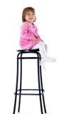 La petite fille s'assied sur une haute présidence Images stock