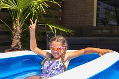 La petite fille s'est habillée dans le maillot de bain et des lunettes de soleil dans la piscine images libres de droits