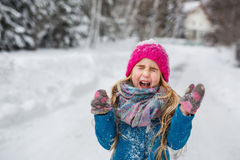 La petite fille s'est habillée dans un manteau bleu et des cris de plaisanterie de chapeau rose pendant l'hiver Photographie stock