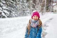 La petite fille s'est habillée dans un manteau bleu et un chapeau rose a fermé ses yeux Images stock