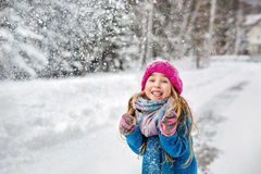La petite fille s'est habillée dans un manteau bleu et un chapeau rose grimaçant Photographie stock
