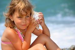 La petite fille s'est penchée la cuvette de seashell à une oreille image stock
