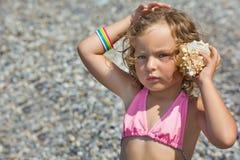 La petite fille s'est penchée la cuvette de seashell à une oreille Image libre de droits