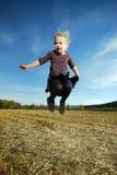 La petite fille saute Photo stock