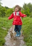 La petite fille saute dans le regroupement Photo stock