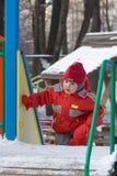 La petite fille se lève sur une pente de glace Images stock