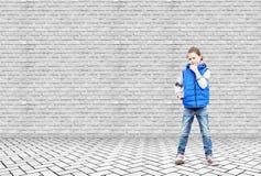 La petite fille se tient dans l'attention à côté du mur de briques photographie stock