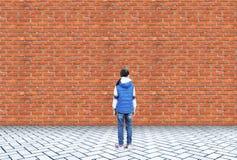 La petite fille se tient dans l'embarras devant un mur de briques image stock