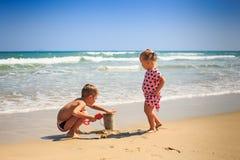 La petite fille se tient et le garçon s'accroupit sur le bord du ressac de vague Photos libres de droits