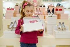 La petite fille se tient et les prises ouvrent la boîte avec des chaussures Images libres de droits