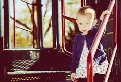 La petite fille se tient sur l'équipement de terrain de jeu Photographie stock