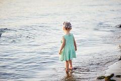 La petite fille se tient sur la berge image libre de droits