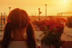 La petite fille se tient sur le balcon regardant le coucher du soleil photographie stock libre de droits
