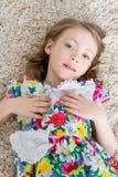 La petite fille se trouve sur le tapis blanc Photographie stock
