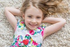 La petite fille se trouve sur le tapis blanc Photographie stock libre de droits