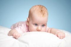 La petite fille se trouve sur un oreiller Photo stock