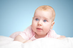 La petite fille se trouve sur un oreiller Photographie stock
