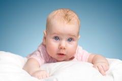 La petite fille se trouve sur un oreiller - nuage Photos libres de droits