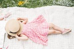 La petite fille se trouve sur un plaid avec un chapeau photo stock