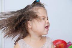 La petite fille secoue la tête éclaboussant des cheveux enfant drôle avec la danse expressive d'émotion images libres de droits