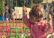 La petite fille seule triste s'asseyant sur l'oscillation en parc, recherche sa maman Photos stock