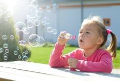 La petite fille souffle des bulles de savon Photos libres de droits