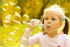 La petite fille souffle des bulles de savon Images stock