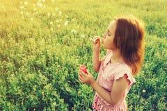 La petite fille souffle des bulles de savon Photos stock